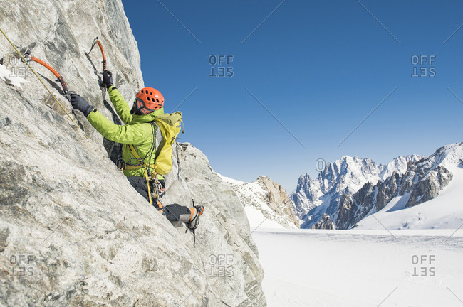Male hiker climbing mountain against clear blue sky during winter