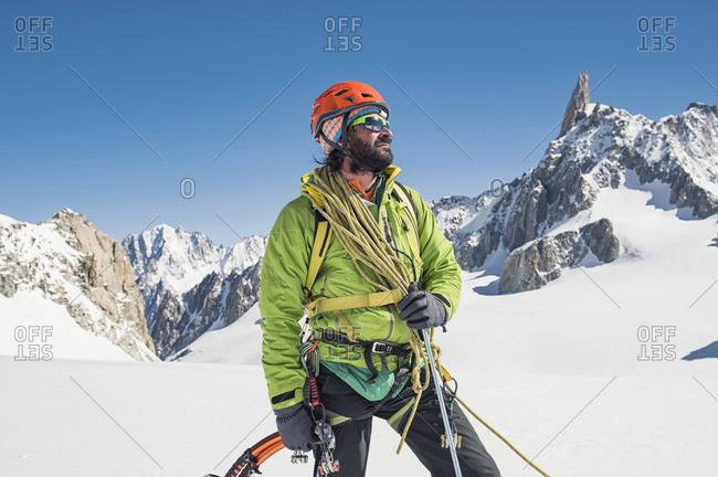 Hiker with climbing equipment standing on snow covered mountain against clear blue sky