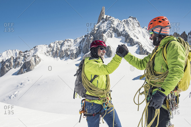 Happy hikers giving high-five while standing on snow covered mountain against clear blue sky