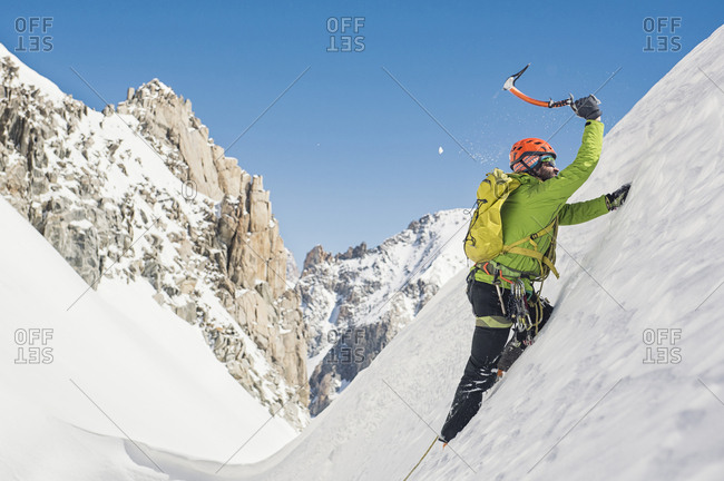 Side view of hiker climbing snow covered mountain against clear blue sky