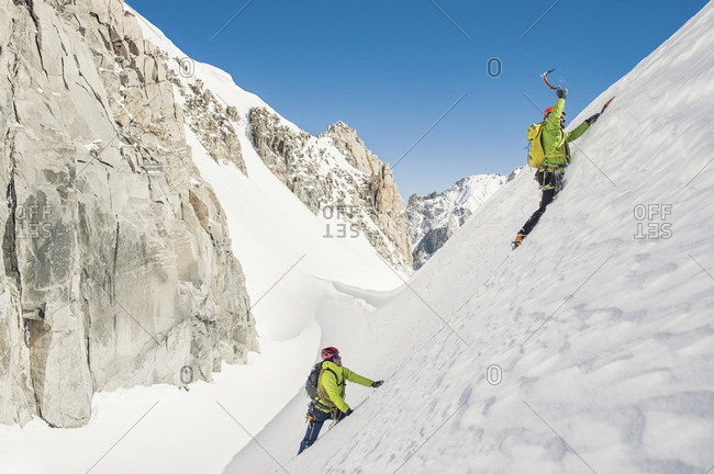 Hikers climbing snow covered mountain against clear blue sky during sunny day
