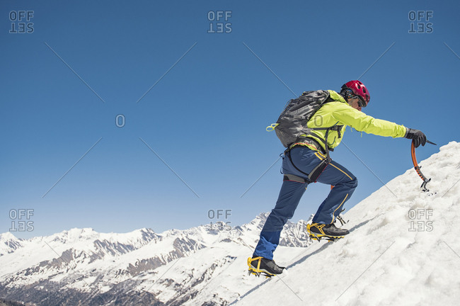 Side view of hiker climbing snow covered mountain against clear blue sky during sunny day