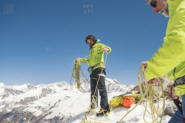 Friends with rope on snow covered mountain against clear blue sky during sunny day