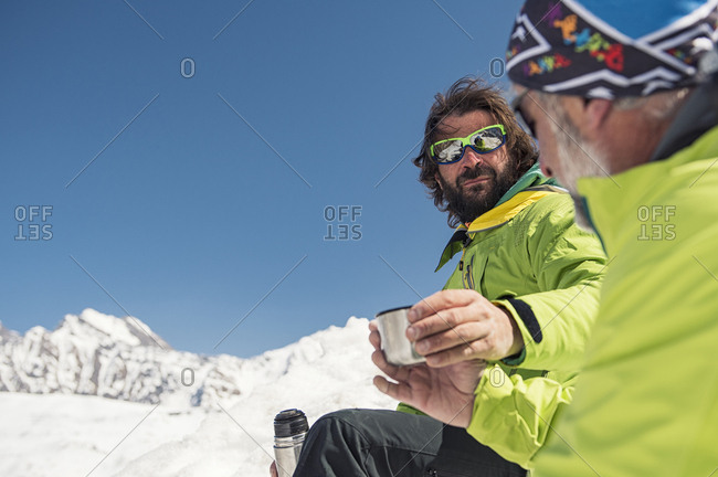 Hikers having drinks on snow covered mountain against clear blue sky during sunny day