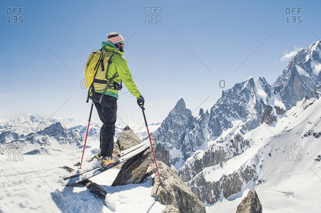 Hiker with skis standing on snow covered mountain against clear blue sky during sunny day
