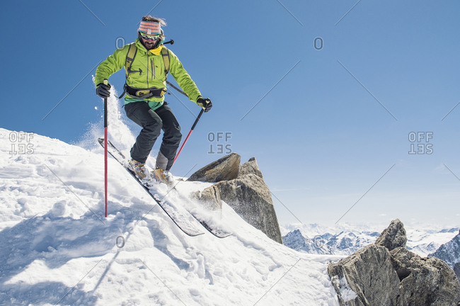 Hiker skiing on snow covered mountain against clear blue sky during sunny day