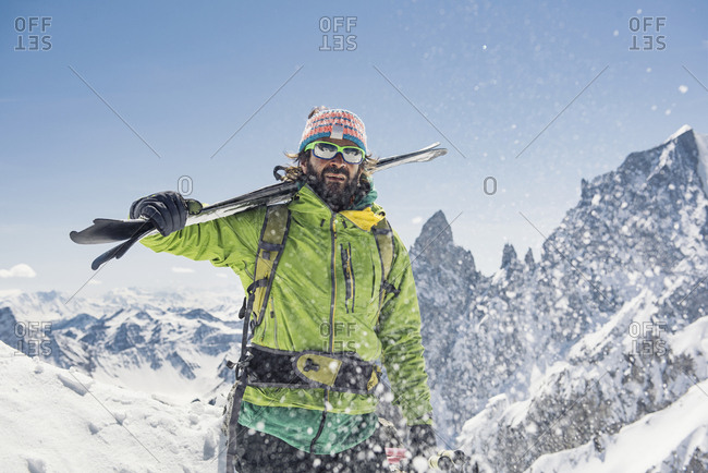 Hiker with skis standing on snow covered mountain against clear sky during sunny day