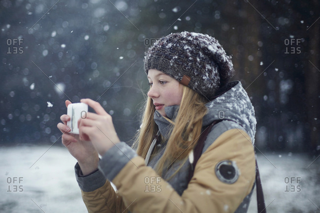 Woman photographing through mobile phone during snowfall