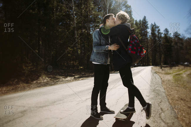 Romantic couple kissing while standing on road in forest during sunny day