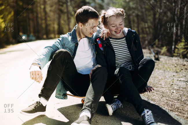 Happy couple sitting on skateboard at road during sunny day