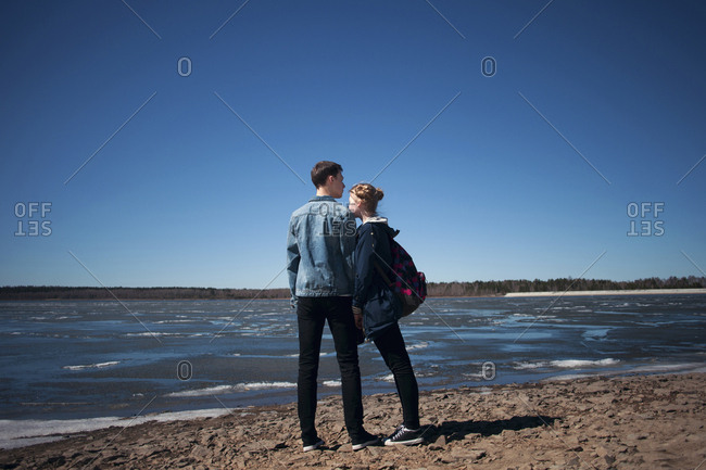 Couple standing at beach against clear blue sky during sunny day