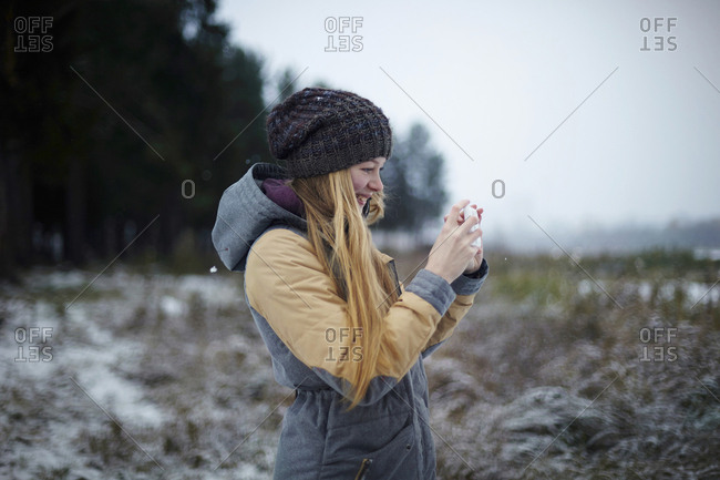 Woman photographing through mobile phone during winter
