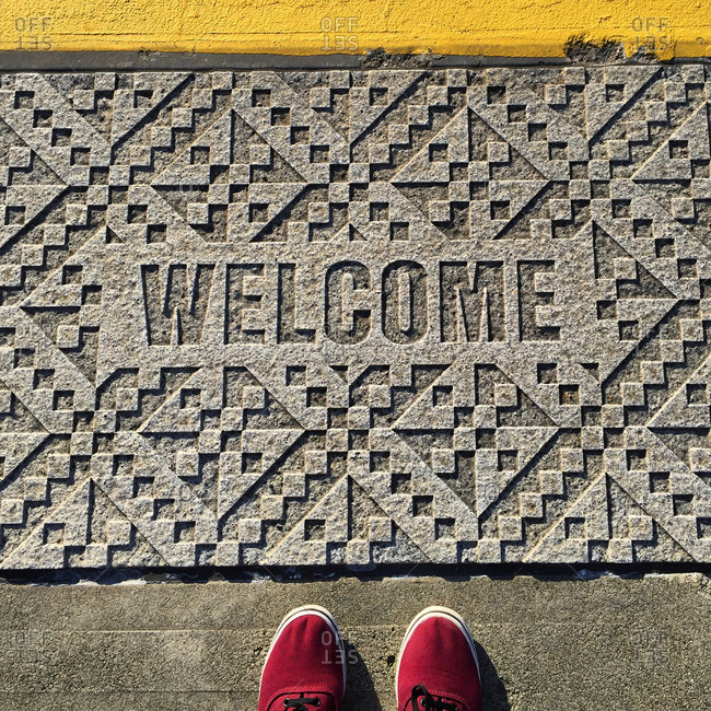 Low section of man standing by welcome text carved on footpath