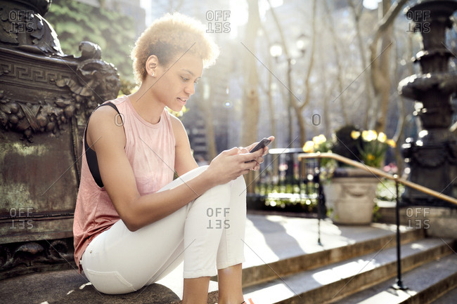 Young woman using mobile phone while sitting on steps