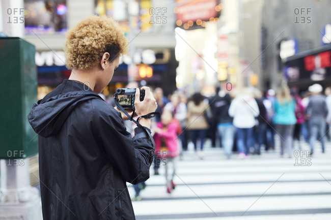 Rear view of young woman photographing on city street