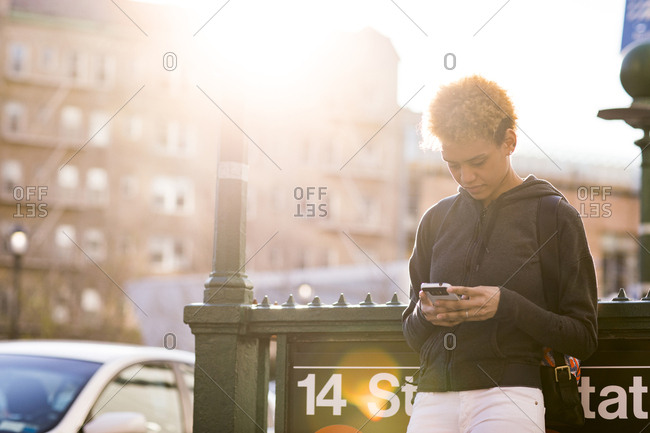 Young woman using smart phone while standing by signpost