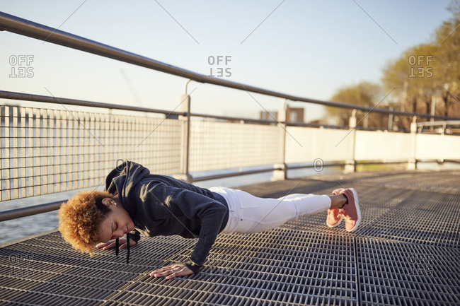 Side view of determined young woman doing push-ups on metallic footpath