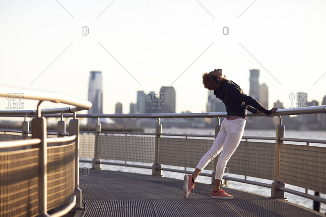 Young woman exercising on footpath by river in city against clear sky