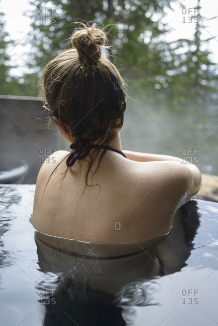 Rear view of woman relaxing in hot spring