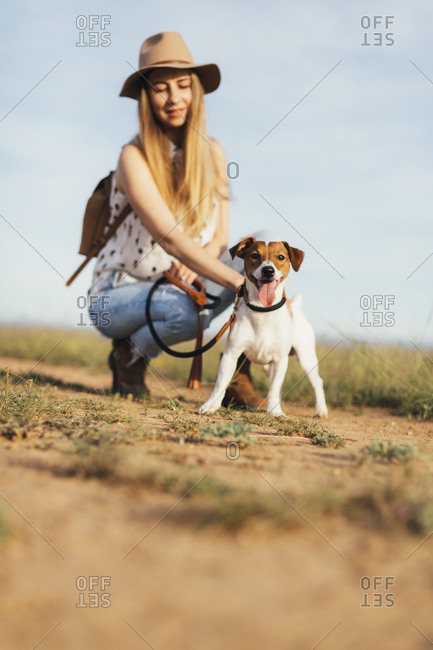 Woman petting dog while crouching at field against sky