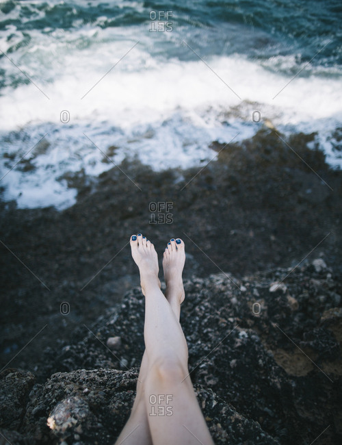 Low section of woman sitting on rock by sea