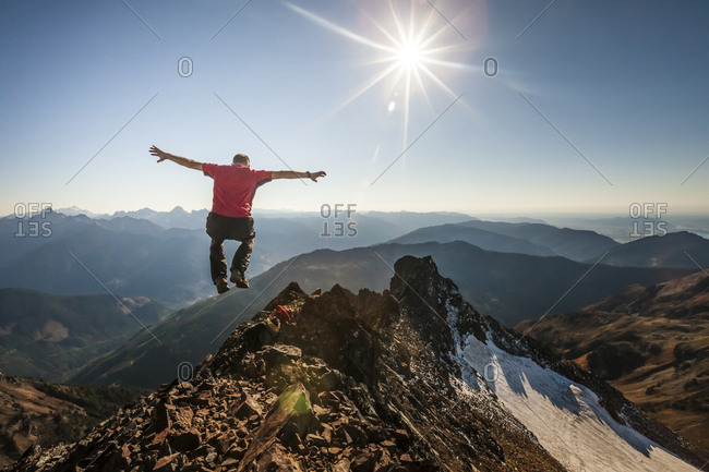 Rear view of hiker with arms outstretched jumping on rocky mountain during sunny day