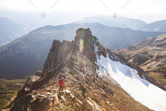 High angle view of male hiker walking on rocky mountains against sky during sunny day