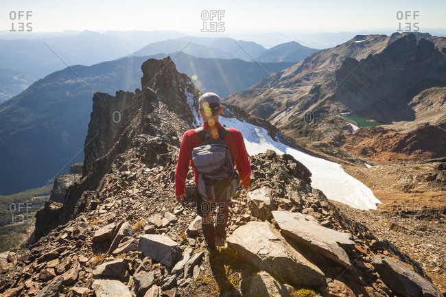 Rear view of male hiker with backpack walking on rocky mountains during sunny day