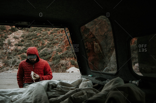 Man holding banana while standing by mini van against mountain