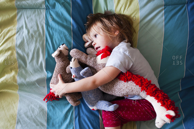 Overhead view of girl with stuffed toys lying on bed at home