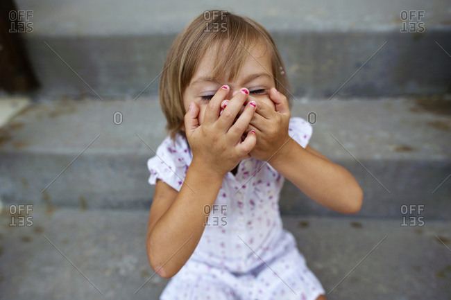 High angle view of girl covering her mouth with hands while sitting on steps