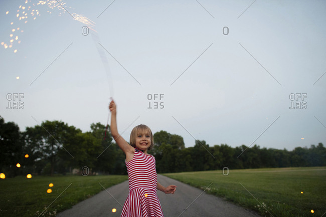Happy girl holding firework while standing on road amidst grassy field at park