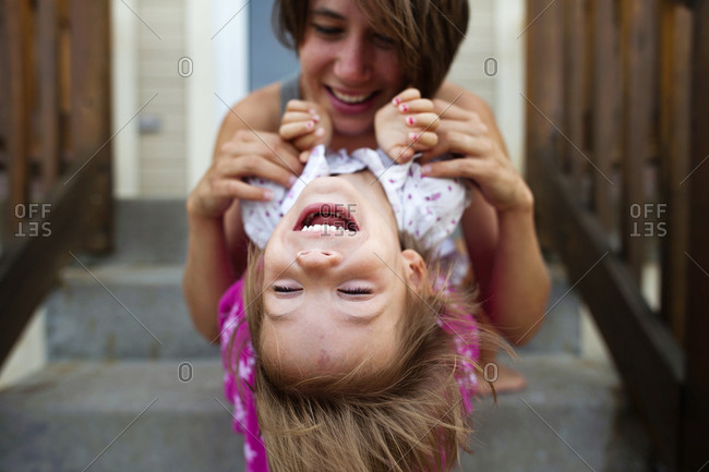 Happy mother playing with daughter while sitting on steps