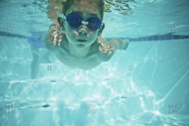 Shirtless boy swimming underwater in pool