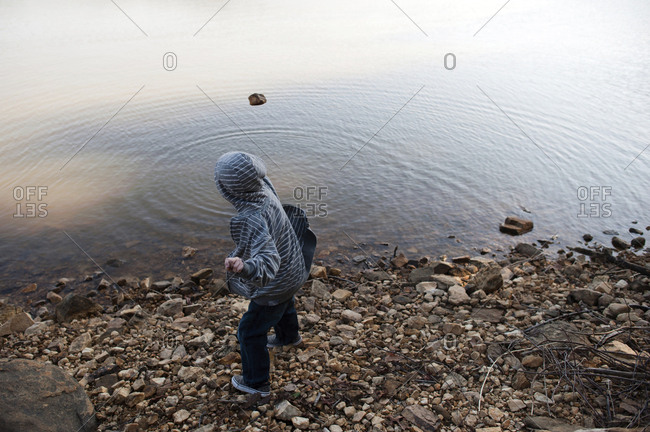 Side view of boy wearing hooded shirt throwing stone in lake