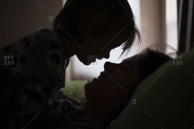 Silhouette mother and daughter looking at each other while relaxing on bed at home