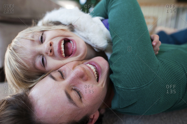 Happy mother embracing daughter while lying on carpet at home