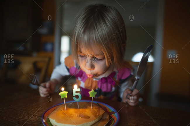Girl blowing candles on pancake