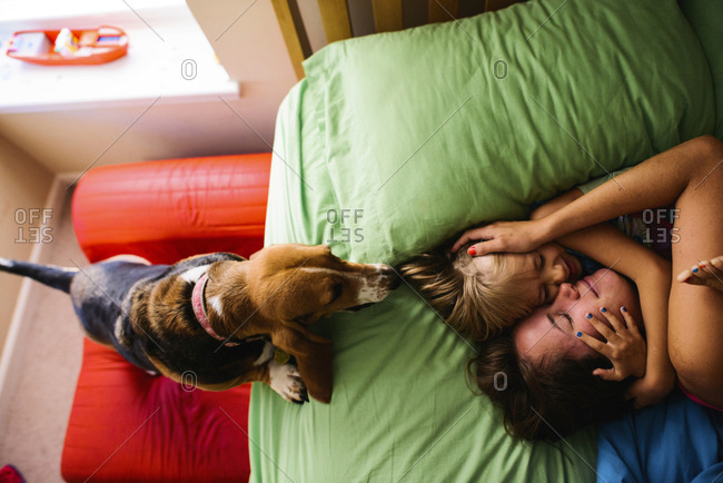 Overhead view of dog looking at mother and daughter embracing on bed at home