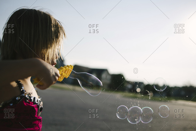 Side view of girl blowing bubble wand at playground against clear sky