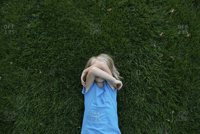 Overhead view of girl covering face while lying on grassy field