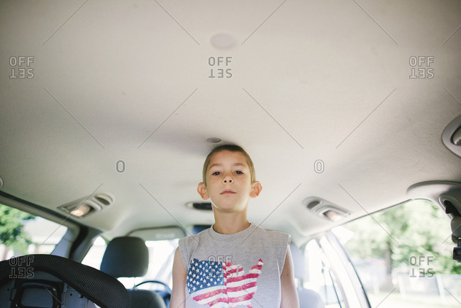 Low angle portrait of confident boy standing in car