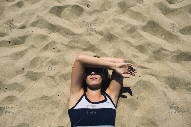 Overhead view of woman covering face while lying on sand during sunny day