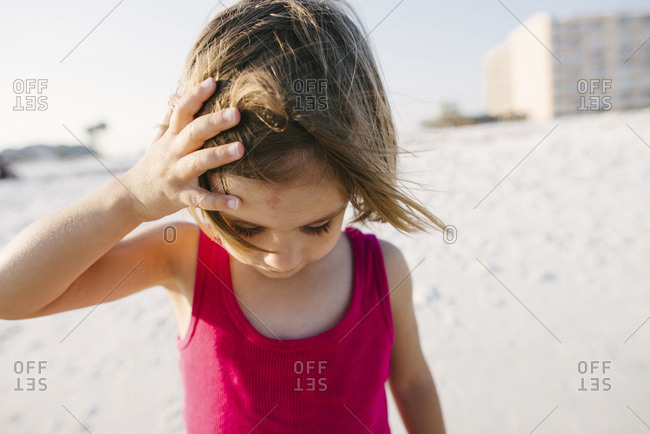 Girl looking down while standing at beach