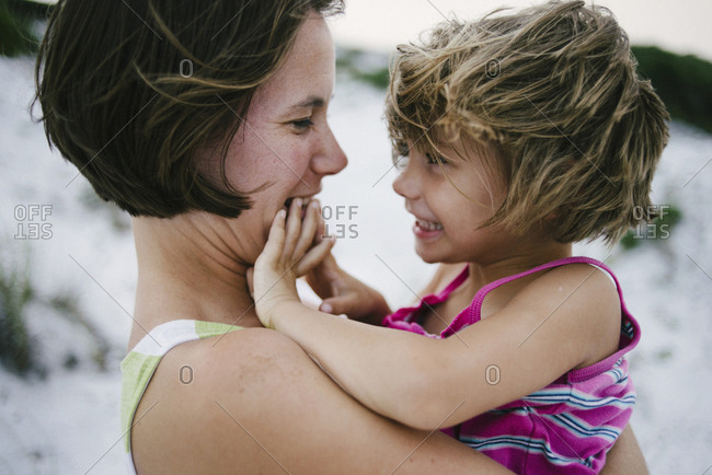 Side view of mother carrying happy daughter at beach