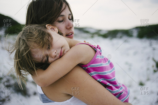 Mother carrying daughter sleeping at beach