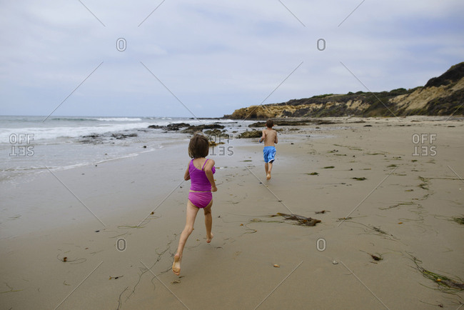 Rear view of siblings running on beach against sky at Crystal Cove State Park