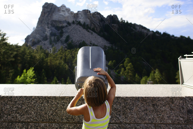 Rear view of girl looking through telescope at Mount Rushmore National Memorial