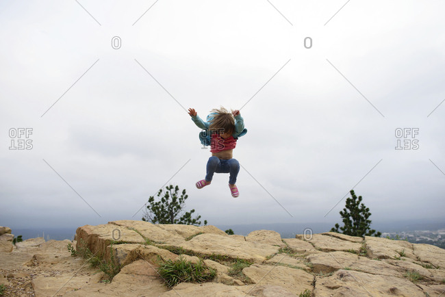 Full length of girl jumping on mountain cliff against sky at Custer State Park