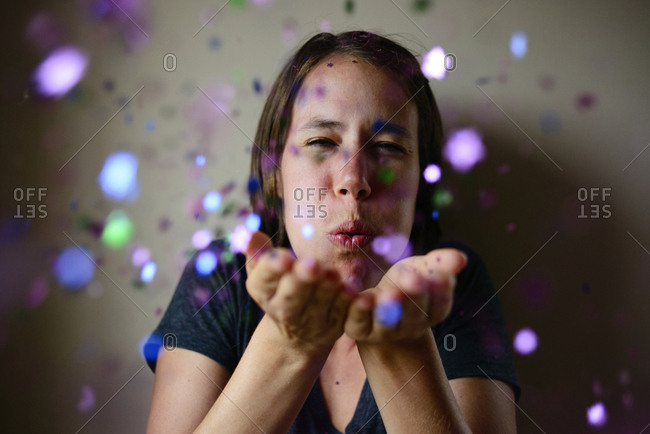 Woman blowing confetti against wall